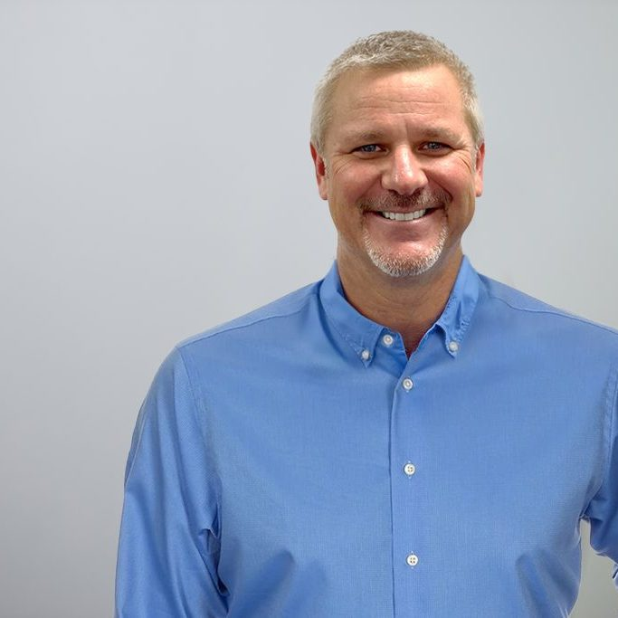 Bert Woerner wearing a blue button up shirt in front of a grey background.